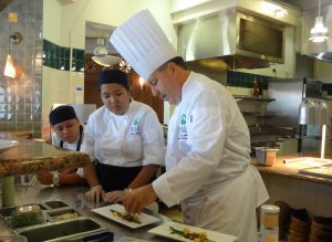 Chef Tom Lelli instructing how to plate salad at UHMC's restaurant. Courtesy photo.