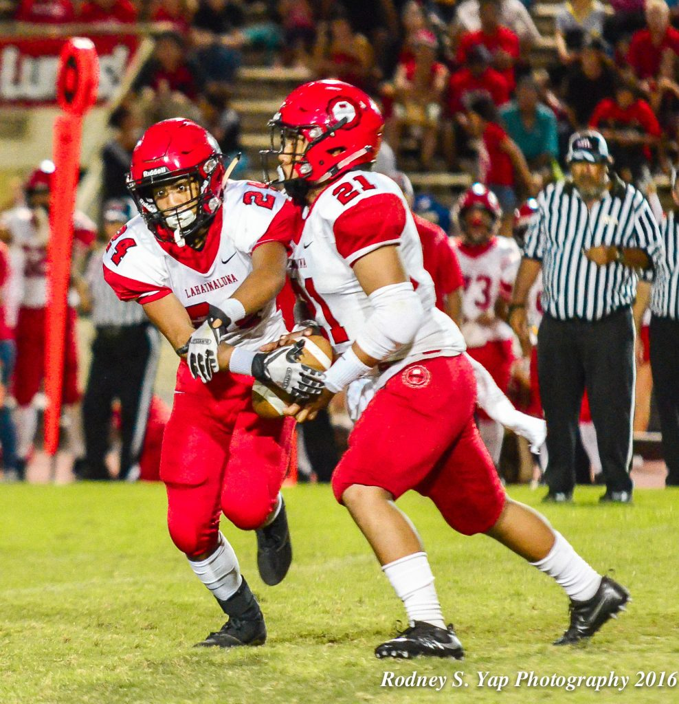 "Lahainaluna's Donavan Defang (21) decides to keep the ball instead of handling it off to teammate out ofthe ""Wildcat"" formation. Photo by Rodney S. Yap."
