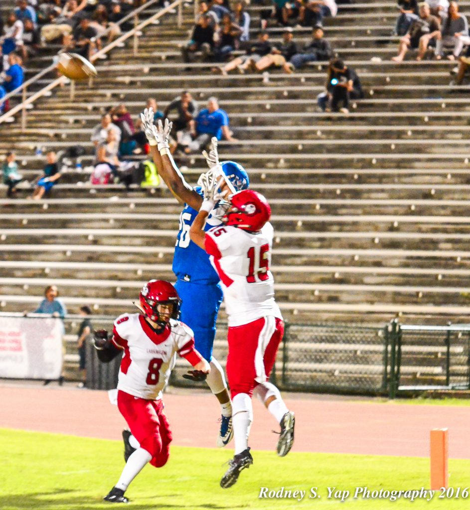 Maui High wide receiver LJ Lindsey grabs this pass from Kainalu Tancayo against Lahainaluna's double coverage for the Sabers' lone touchdown Saturday. Photo by Rodney S. Yap.