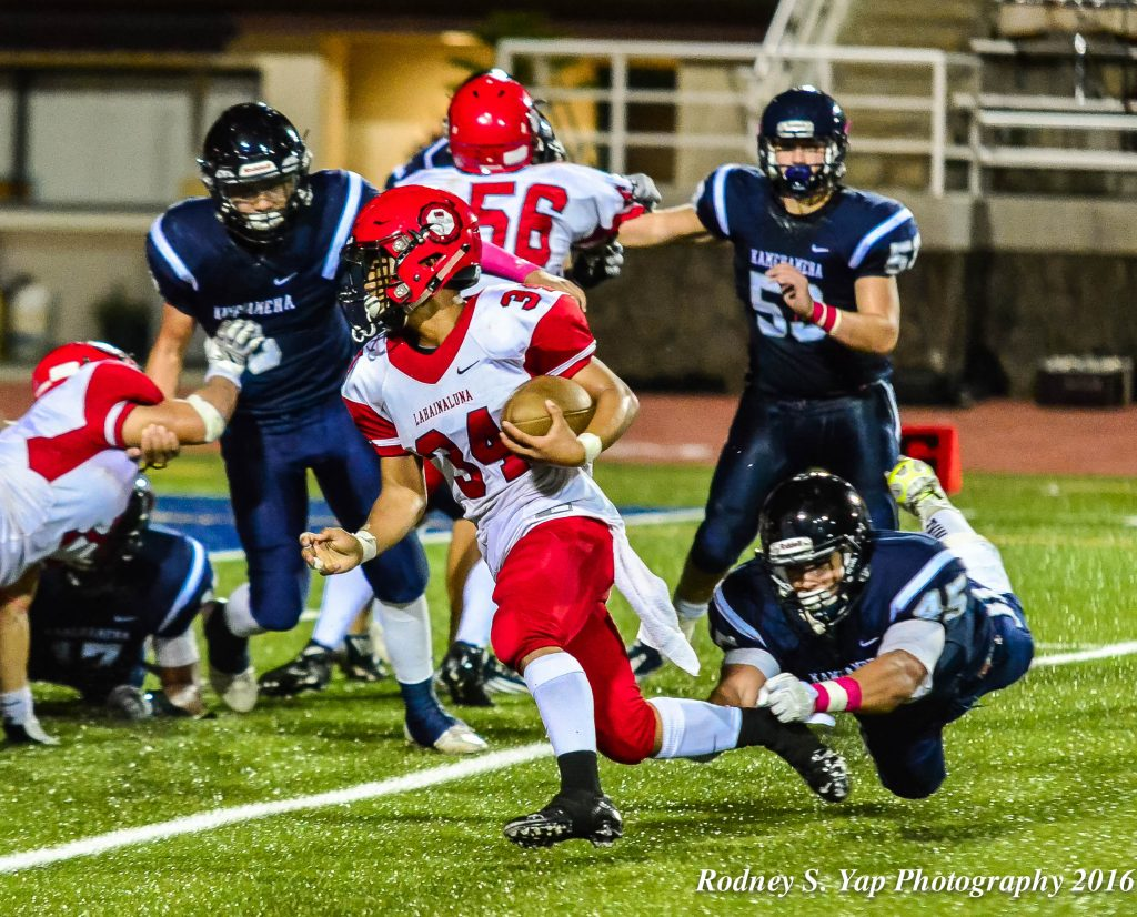 Lahainaluna's Radon Sinenci (34) avoids the outstretched arms of KS-Maui linebacker Kupono Duarte en route to scoring a touchdown. Photo by Rodney S. Yap.