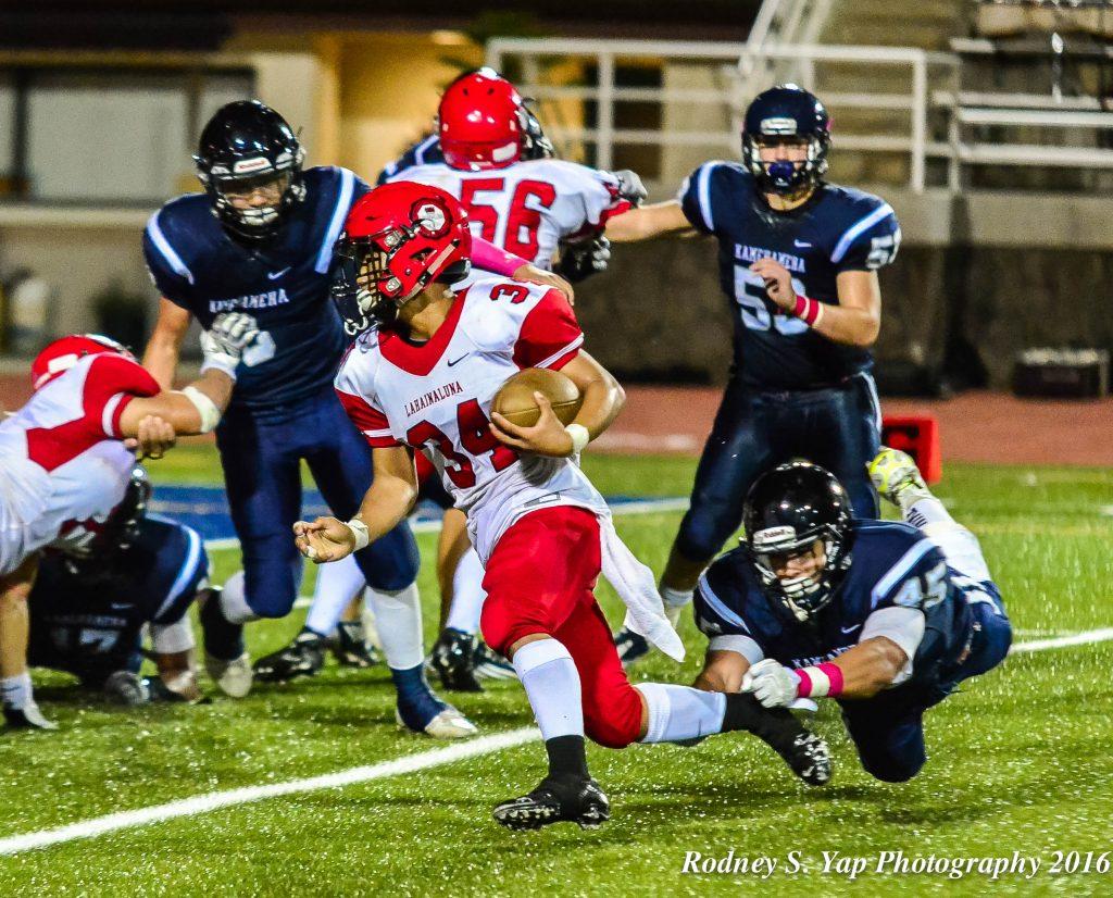 Lahainaluna's Radon Sinenci (34) avoids the outstretched arms of KS-Maui linebacker Kupono Duarte en route to scoring a touchdown. Photo by Rodney S. Yap.