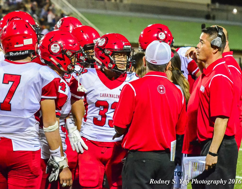 Lahainaluna offensive coordinator Garret Tihada (right) talks to his offensive personnel during a timeout Saturday against Kamehameha Maui. Photo by Rodney S. Yap.