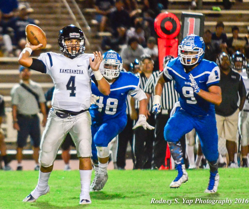 Kamehameha Maui quarterback Kainoa Sanchez hurries to getnridmof this ball as Maui High's Kahoku Kealoha (9) rushes from the backside. Photo by Rodney S. Yap.