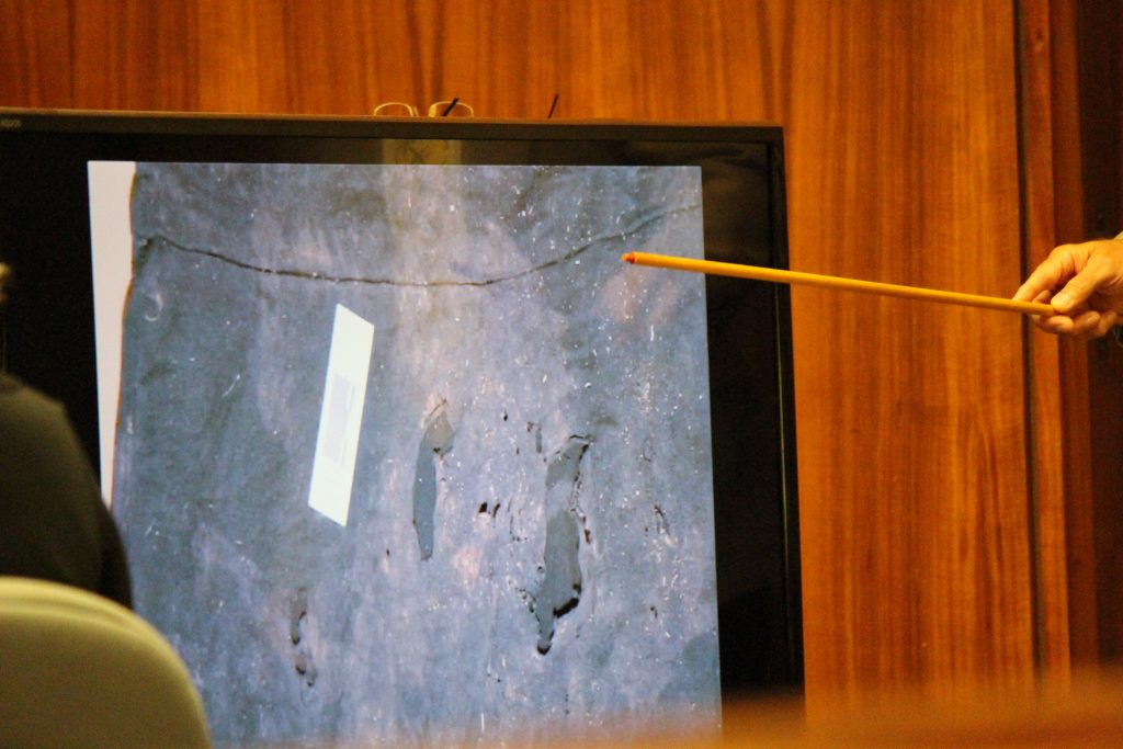 Anthony Earls, evidence specialist with the Maui Police Department describes holes and staining observed on a black skirt recovered from Nuaʻailua Bay. Photo by Wendy Osher.