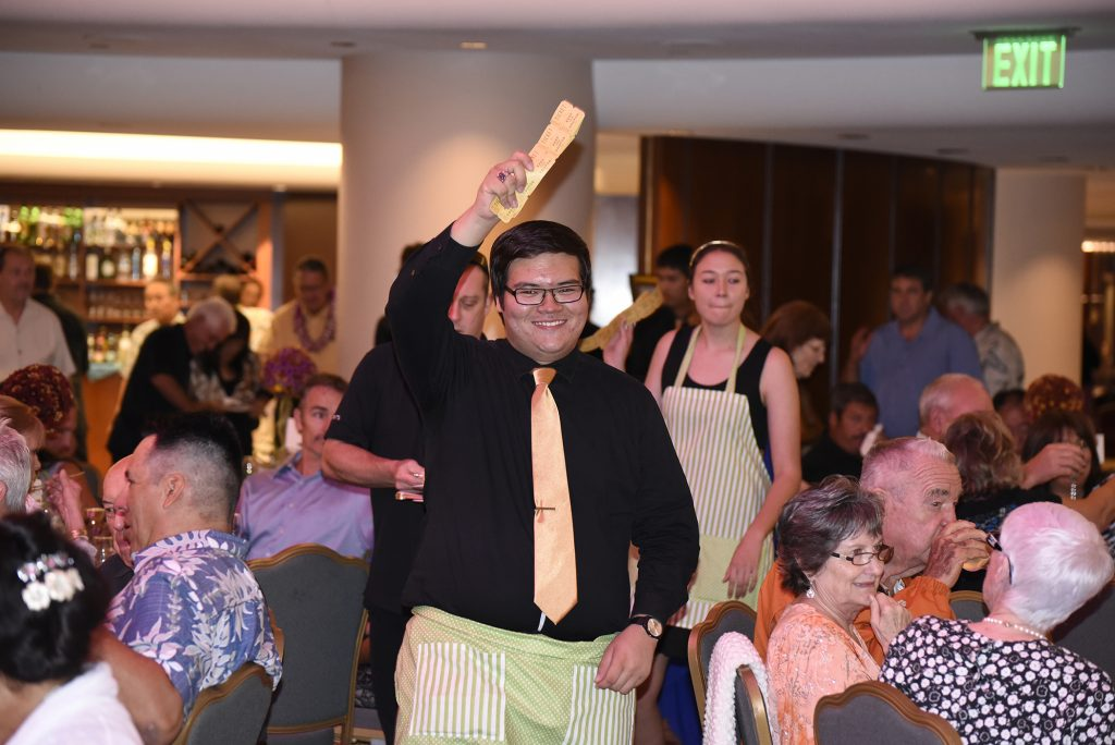 Former St. Anthony Junior-Senior High School Student Body President Micah Leval (center), a 2016 alum, seeks support from attendees during the 2015 Strength in Unity Gala at the Kamehameha Golf Clubhouse. Funds raised at this year's event set for Friday, November 11, will go towards student tuition assistance.