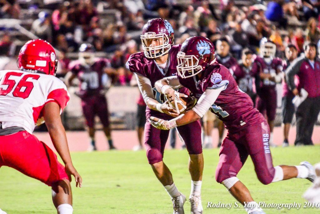 Baldwin High School quarterback Chayce Akaka prepares to fake a handoff to Daniel Corpuz and keep the ball as Lahainaluna's Viliami Hafoka looks on. Photo by Rodney S. Yap.