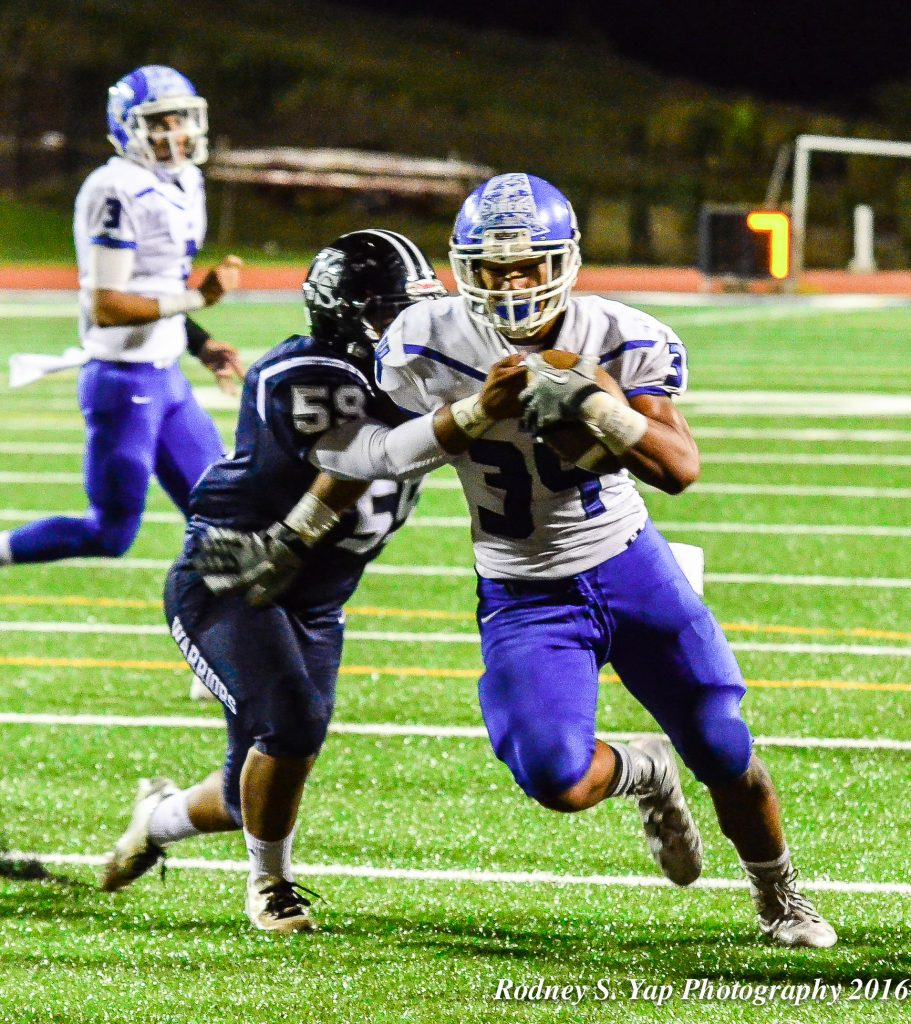 Maui high School's Hanisi Lotulelei (34) shakes a would-be Warrior tackler en route to scoring his third rushing touchdown of the game Friday at Kamehameha Maui. Photo by Rodney S. Yap.