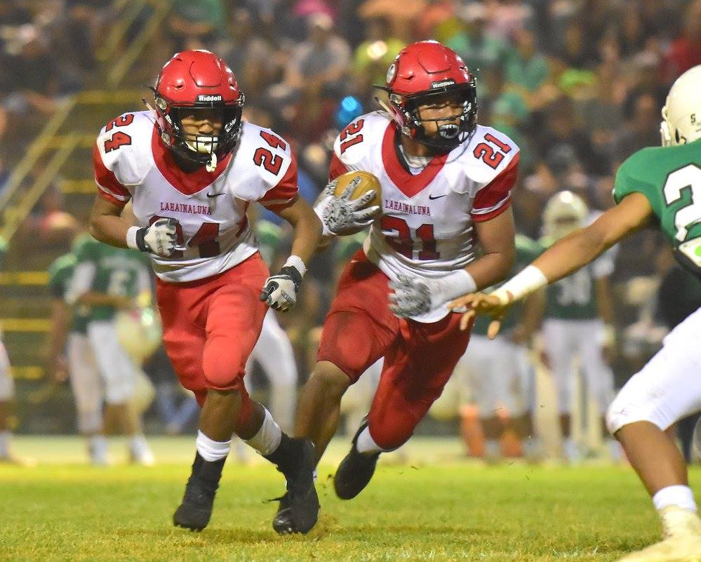 Lahainaluna's Donavan Defang scored a pair of touchdowns in a span of 39 seconds in the third quarter to help the Lunas beat Konawaena Saturday, 28-14. Teammate Elijah Ragudo (24) looks to make a block for Defang. Photo by Glen Pascual.