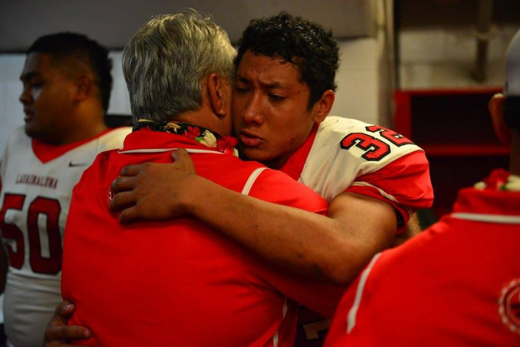 Lahainaluna co-head coach Bobby Watson shares a moment with senior Josaiah Sombelon-McEwen, who had five tackles in the championship game against Kapaa, including one sack for minus 8 yards. Photo by Glen Pascual.