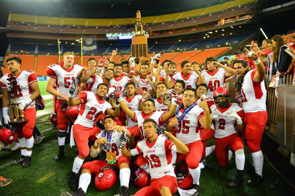 The Lunas celebrate with the Division II trophy on the field at Aloha Stadium last week. Photo by Rodney S. Yap