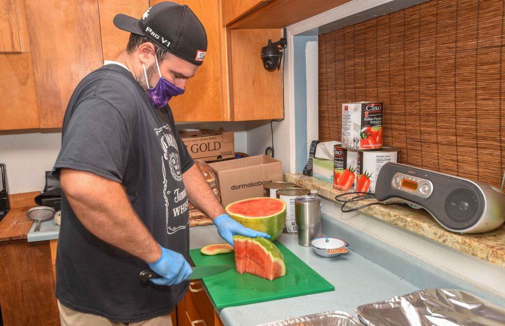 Michael Clark cuts watermelon for homeless.